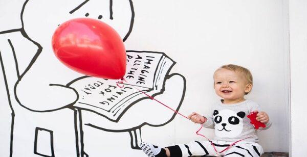 happy baby boy with read balloons e1615651600996 - 8 استایل لباس پسر بچه زیبا در نوروز سال 1400